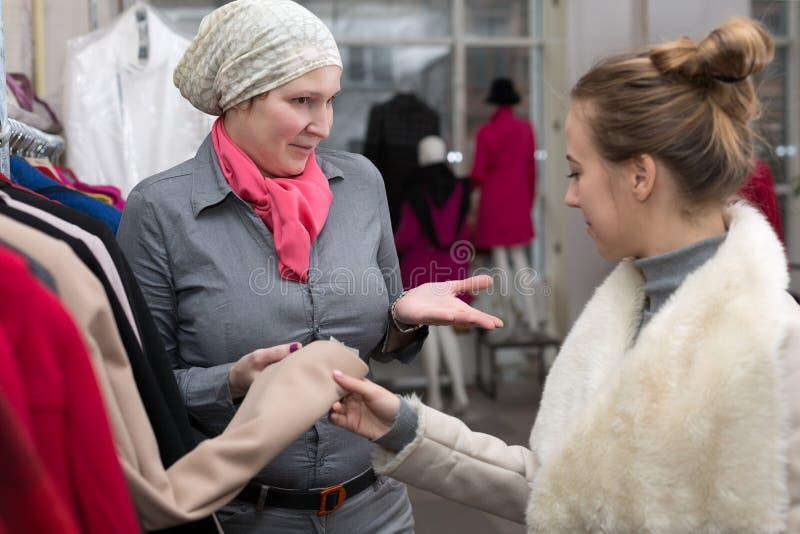 显示夹克的品种女售货员对顾客在零售店 库存图片