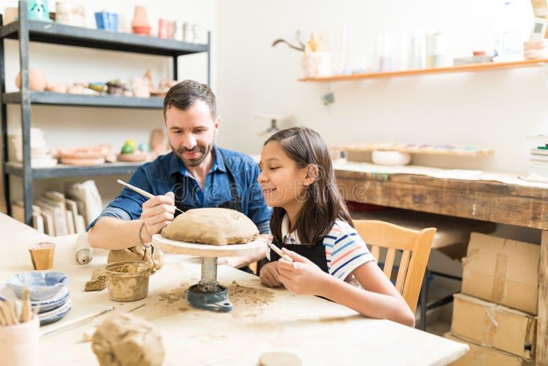 显示女孩的陶瓷工做设计在黏土在瓦器演播室 免版税库存照片