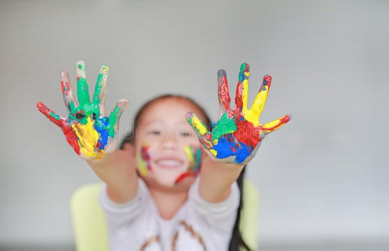 显示她五颜六色的手和面颊的微笑的小快乐的女孩被绘在孩子屋子里 在婴孩手的焦点 库存图片