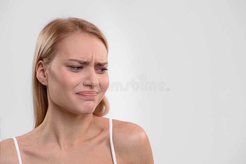 显示她关于某事的白肤金发的女孩反感 免版税库存照片