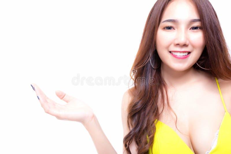 显示她喜爱的产品,胸罩的迷人的美丽的年轻女人 免版税库存照片