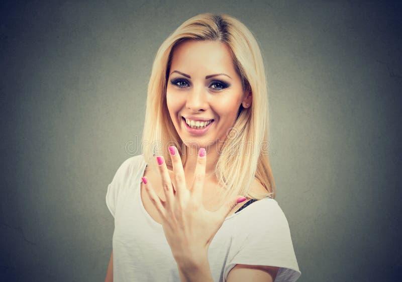 显示她完善的修指甲或五个手指姿态的激动的少妇 库存照片