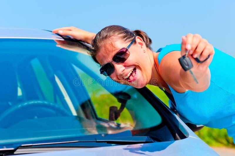 显示她新的汽车的钥匙愉快的妇女 免版税库存照片