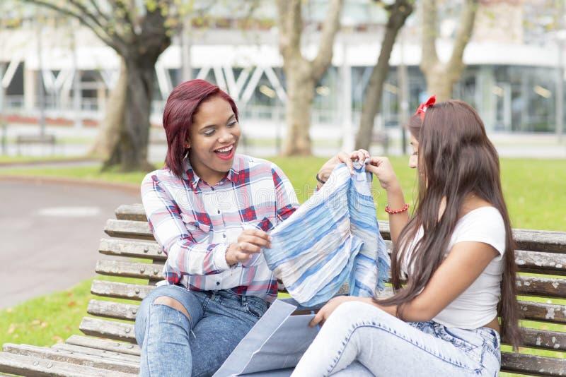 显示她新的衣裳的微笑的妇女对她的朋友 免版税库存照片