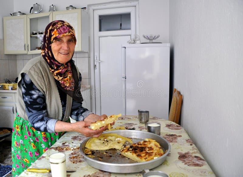 显示她的传统Gorani乳酪饼的愉快的微笑的资深妇女 免版税库存照片