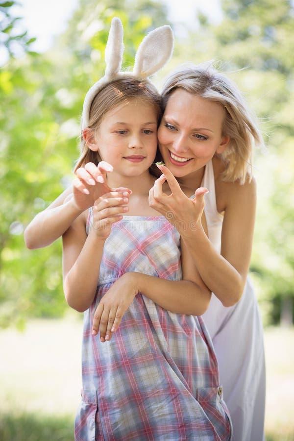 显示她的女儿小的昆虫的母亲 免版税库存照片