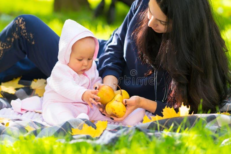 显示她的婴孩新鲜的秋天苹果的年轻母亲 库存图片