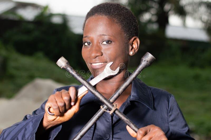 显示她的工具的年轻技工 免版税库存图片