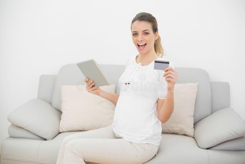 显示她的片剂和信用卡的欢呼的孕妇看照相机 免版税库存照片