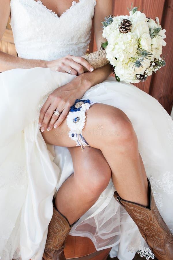 显示她的牛仔靴的新娘和袜带和花束 免版税图库摄影