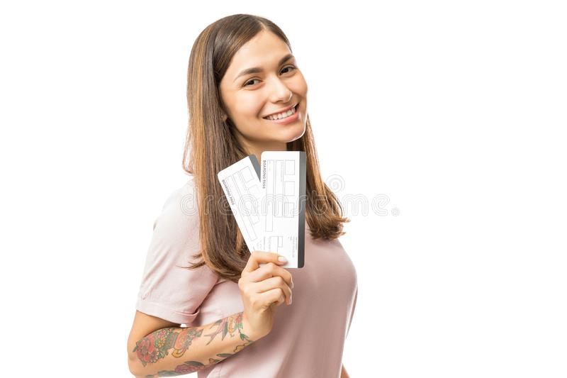 显示她的登舱牌票的愉快的少妇 免版税库存图片
