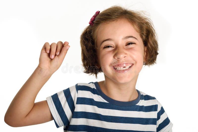 显示她的第一颗下落的牙的愉快的小女孩 免版税库存照片