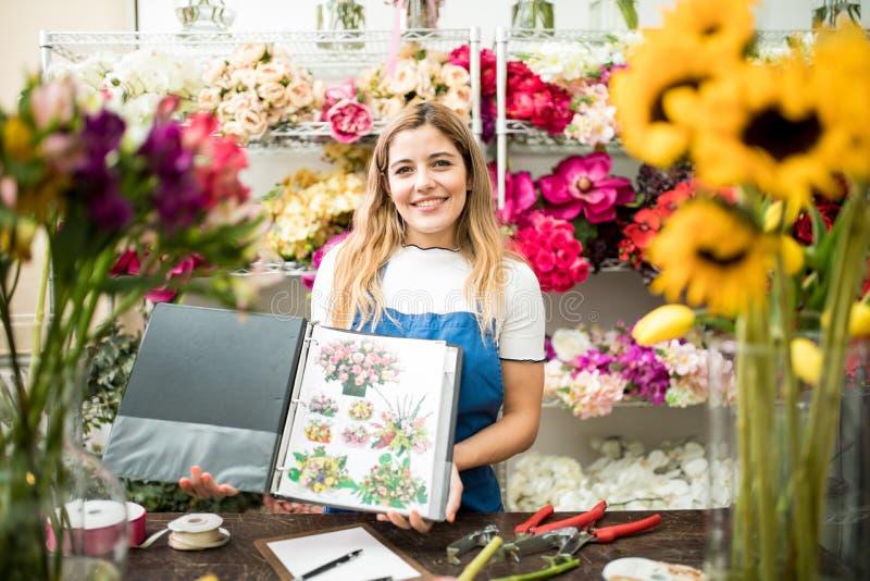 显示她的编目的Floristry专家 免版税库存照片
