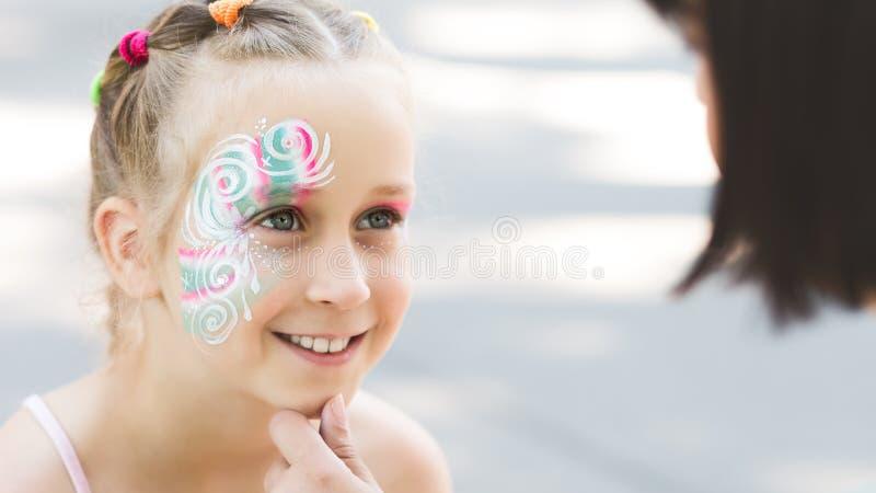 显示她的脸蛋漂亮绘画的逗人喜爱的女孩对妈妈 库存图片