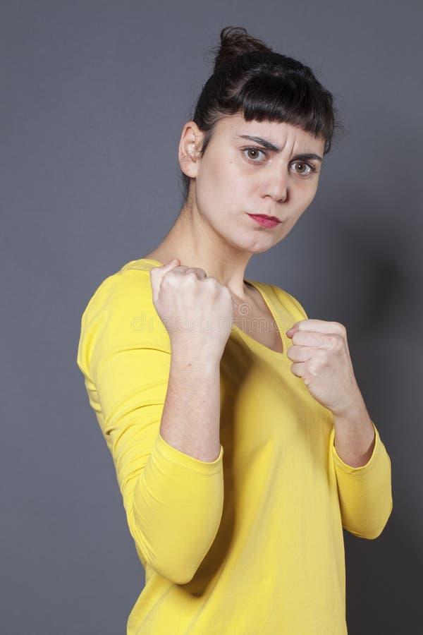 显示她的自卫的不快乐的20s妇女拳头 免版税库存照片