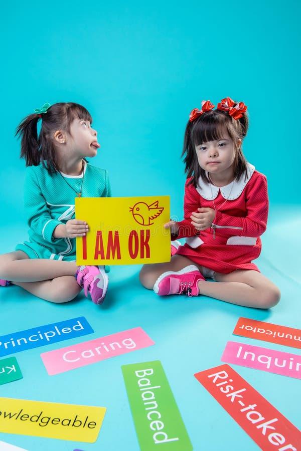 显示她的舌头的聪慧的小女孩,当拿着海报时 免版税库存照片