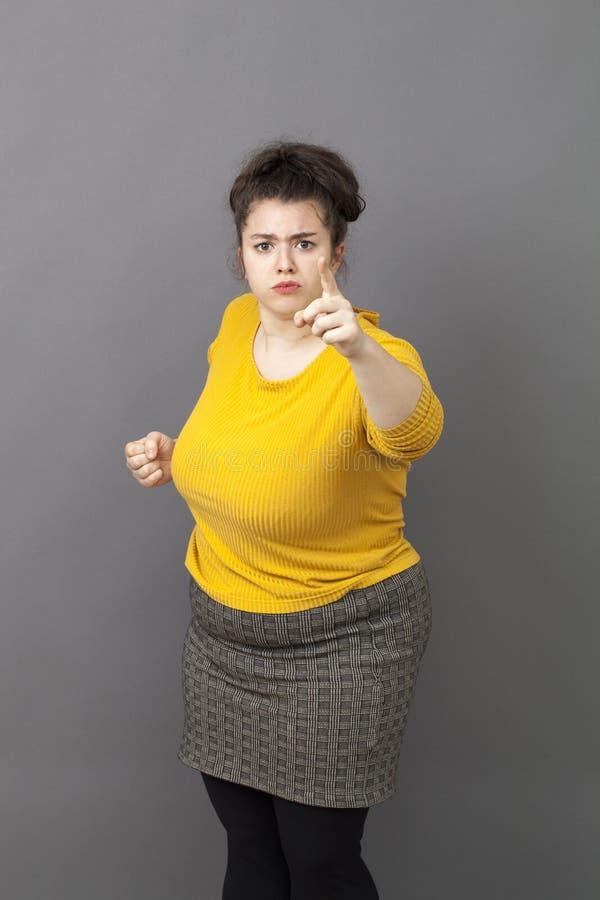 显示她的索引和拳头的独裁的20s肥胖妇女谴责 免版税库存图片