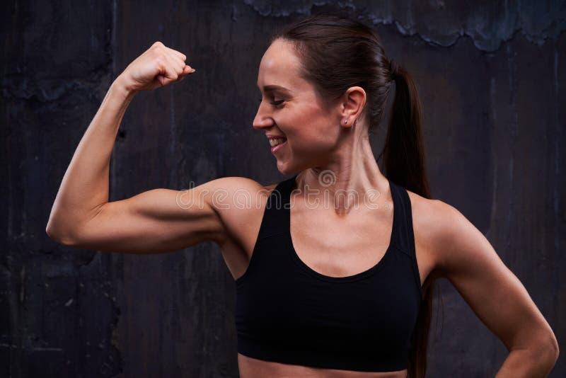 显示她训练的身体的强有力的运动的妇女在照相机iso 免版税库存照片