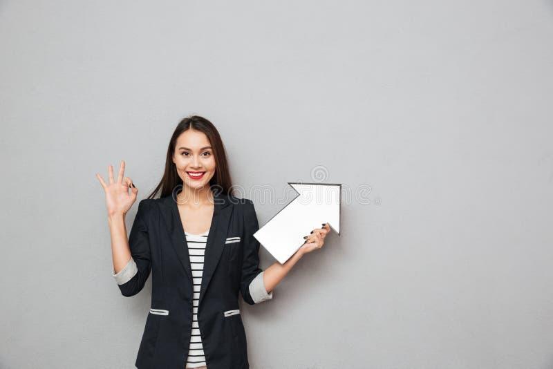 显示好标志和指向的微笑的亚裔女商人 免版税库存照片