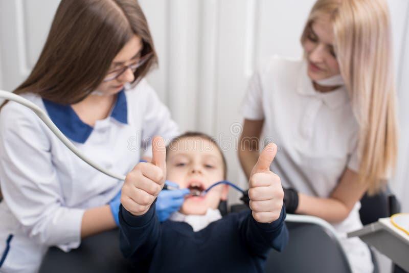 显示好类的赞许姿态孩子,当审查和工作在男孩患者的牙医 免版税库存图片
