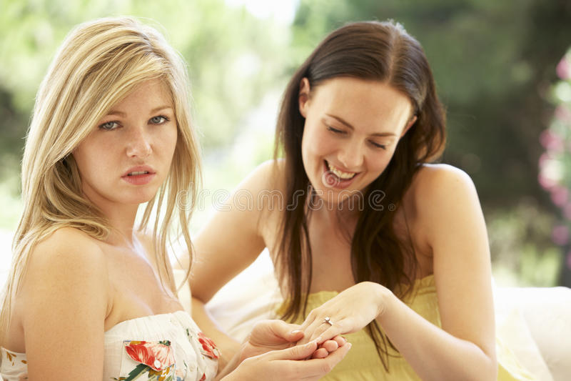 显示嫉妒的朋友定婚戒指的少妇 库存照片