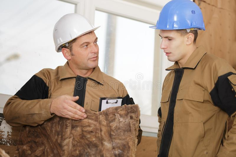 显示学徒吸收体墙壁的建造者夹心板 免版税库存照片
