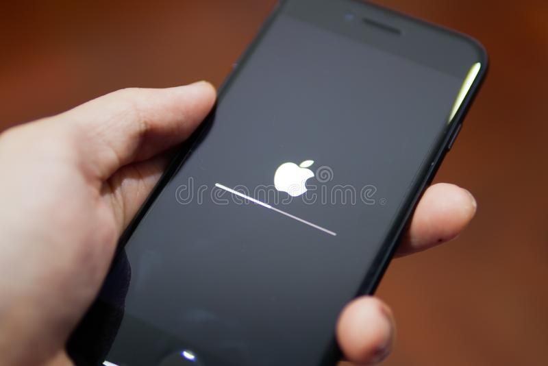 显示它的有苹果计算机商标的苹果计算机iPhone 7屏幕,当更新它对iOS 12的软件 免版税库存照片