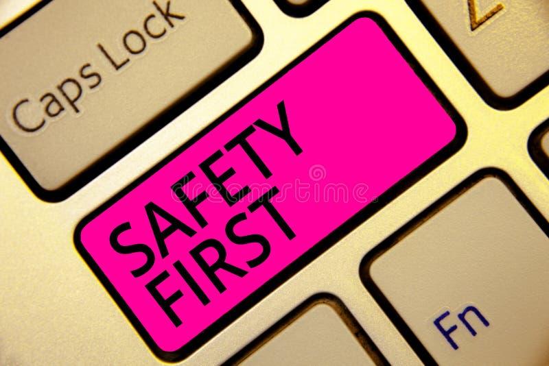 显示安全第一概念性照片的文本标志避免活所有多余的风险安全地是仔细的薪水注意键盘桃红色钥匙 免版税图库摄影