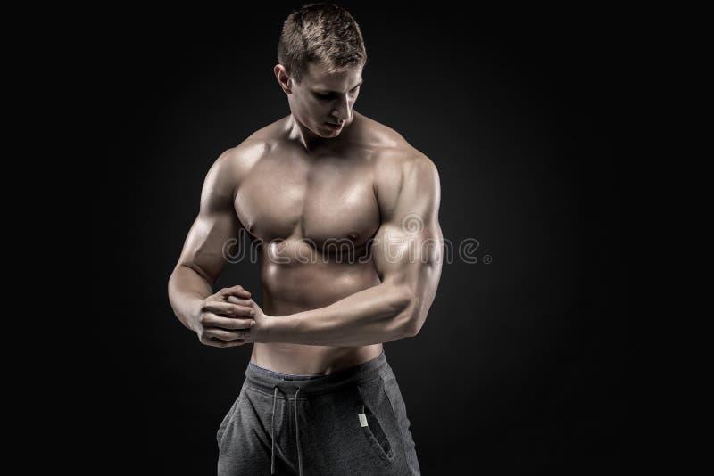 显示完善的肩膀,二头肌,三头肌,胸口的惊人的肌肉人 免版税库存照片
