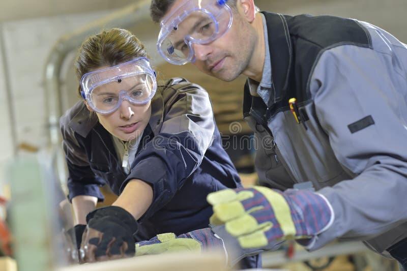 显示实习生木匠业工作的辅导员 免版税图库摄影