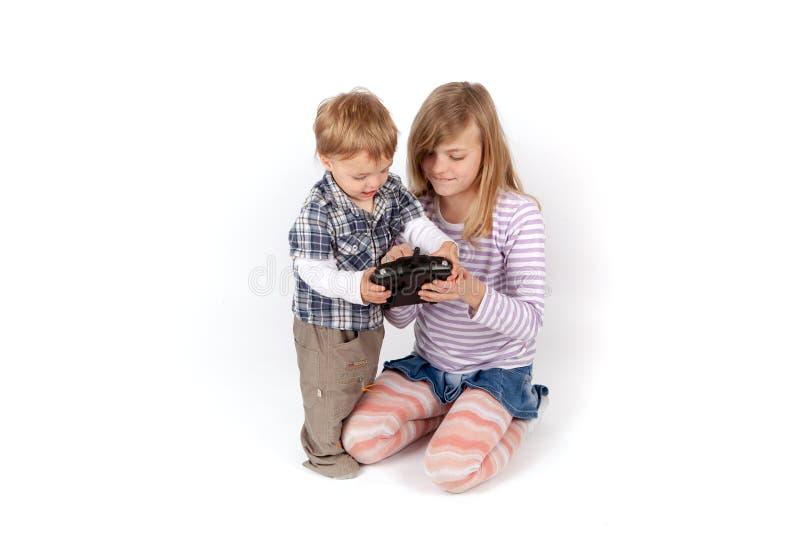 显示寄生虫的女孩遥控对她的小兄弟 免版税库存图片