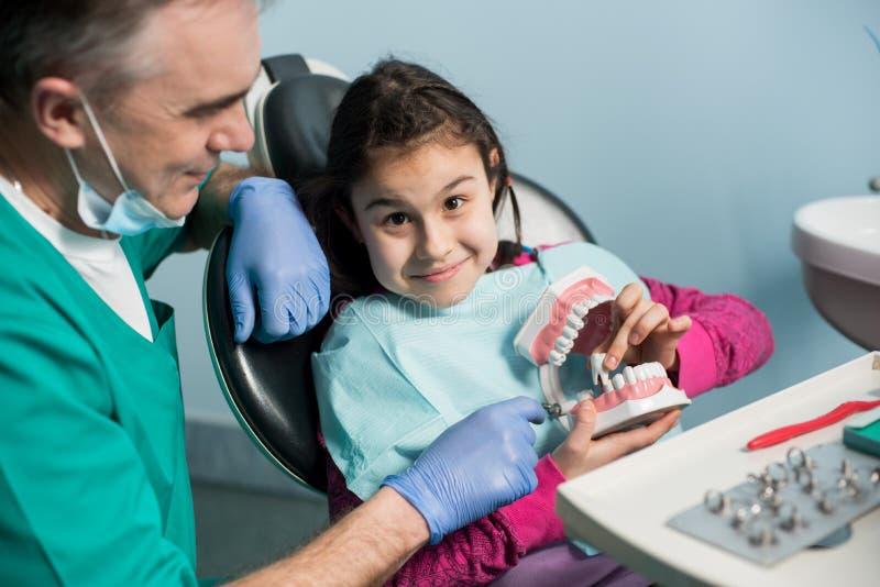 显示对女孩的小儿科牙医在牙医椅子牙齿下颌模型在牙齿办公室 免版税图库摄影