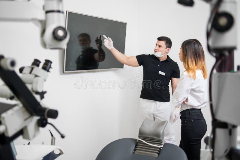 显示对女性患者她的在计算机显示器的男性牙医牙齿X-射线图象在一个牙齿诊所 免版税库存照片