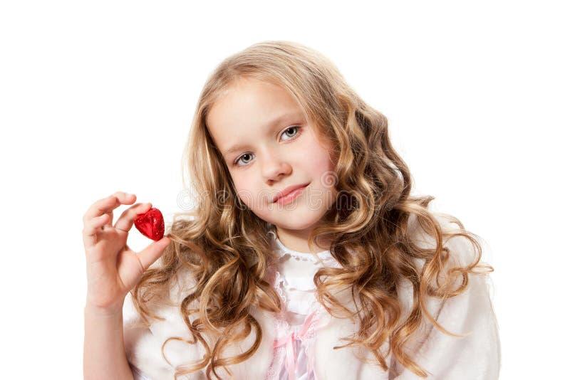显示巧克力糖的可爱的小女孩 免版税库存图片
