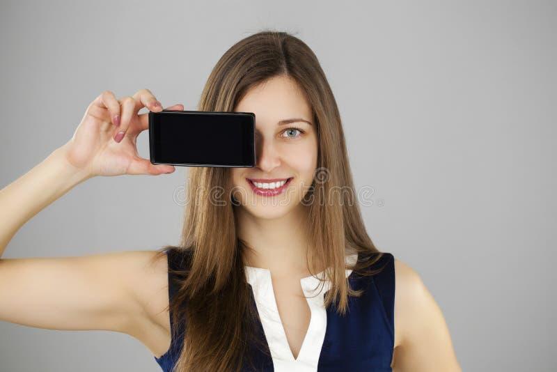 显示巧妙的电话的俏丽的浅黑肤色的男人 免版税图库摄影