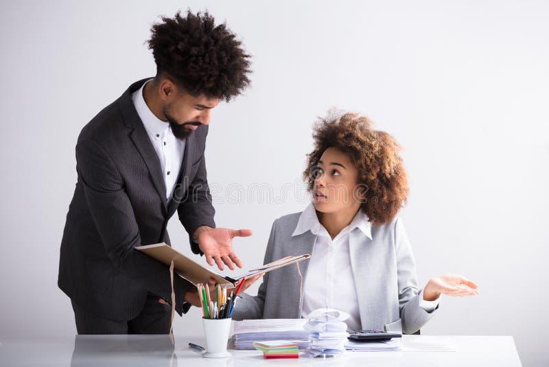 显示差错的商人对他的女性同事 免版税库存图片