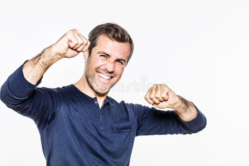 显示幸福、成功与乐观和能量的兴奋的年轻人 免版税库存照片