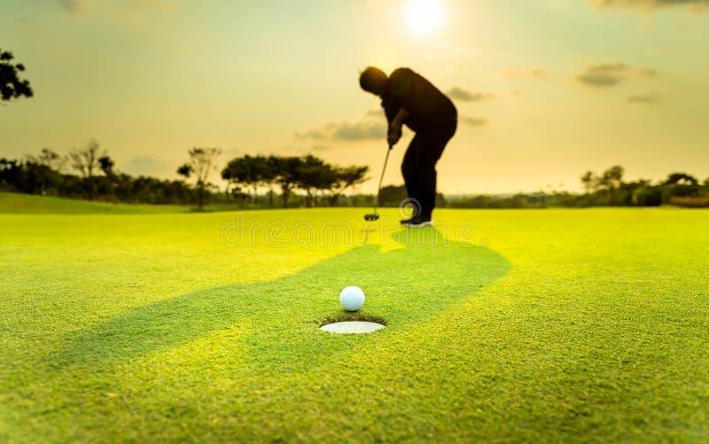 显示幸福的剪影高尔夫球运动员,当胜利在比赛,在绿草的白色高尔夫球有迷离背景 库存图片
