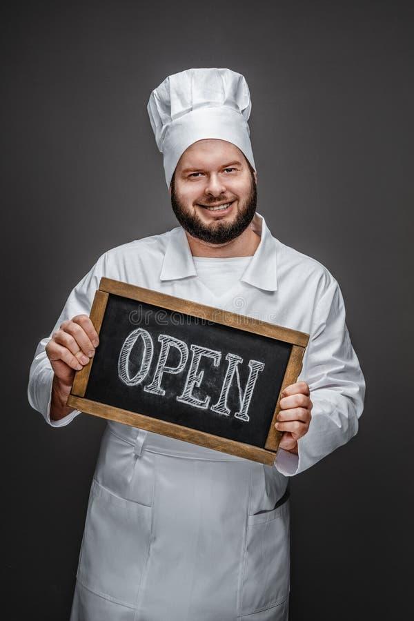 显示开放文字的友好的厨师 库存图片