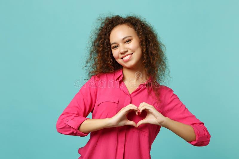 显示形状心脏用手的桃红色便服的微笑的迷人的非洲女孩隔绝在蓝色绿松石墙壁上 库存图片