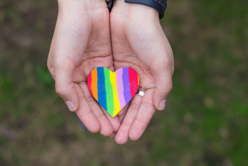 显示彩虹心脏的手 免版税库存照片