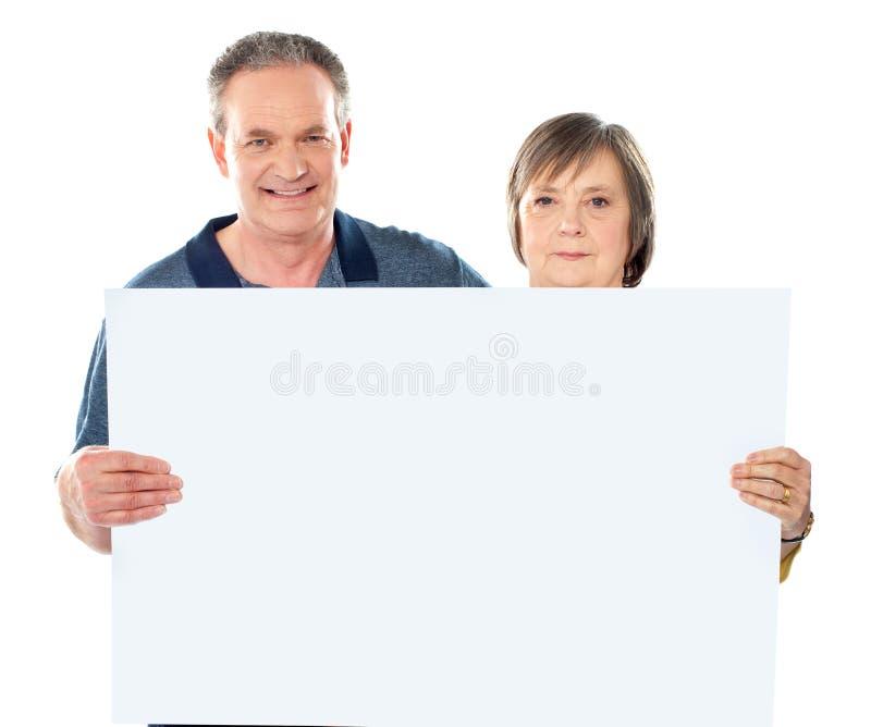 显示微笑的变老的横幅空白夫妇 免版税库存图片