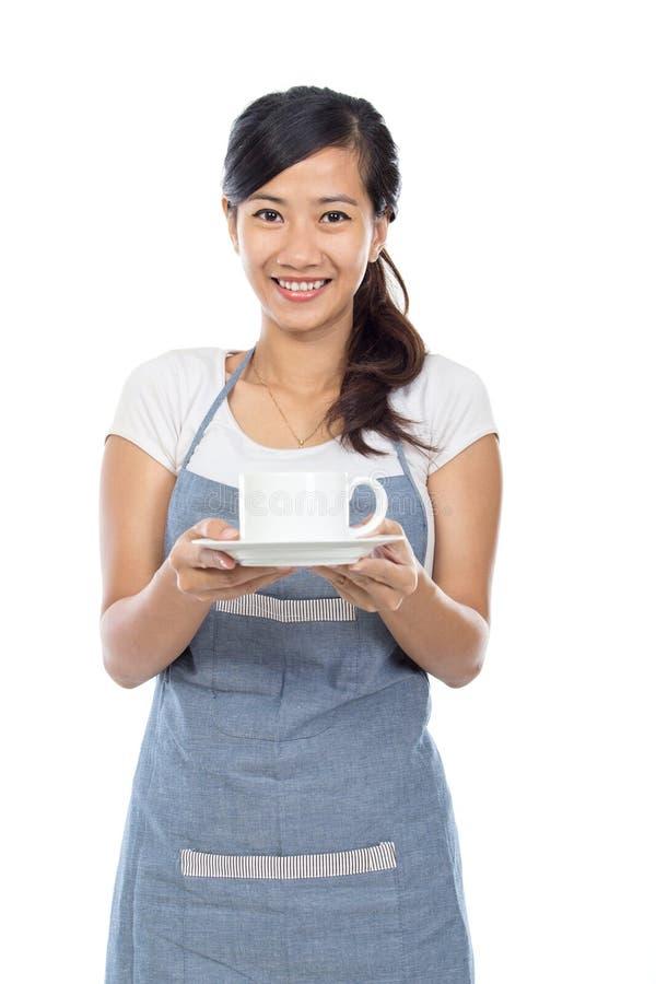 显示微笑的女服务员白人妇女的背景barista咖啡馆咖啡杯重点查出的服务界面 免版税库存照片