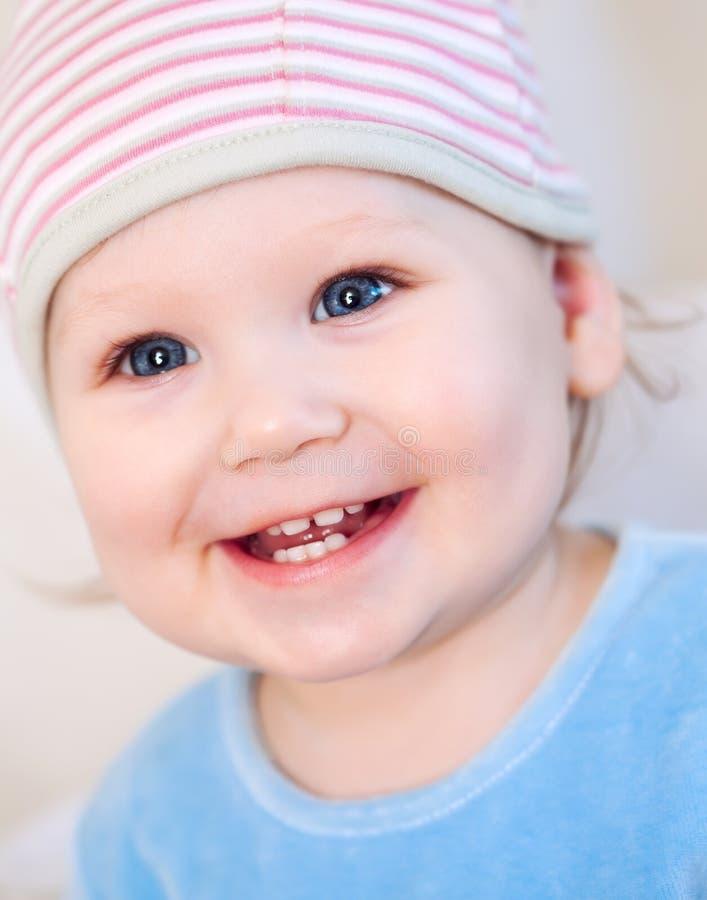 显示微笑的牙佩带的女婴帽子 免版税图库摄影