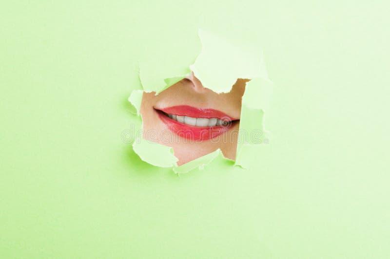 显示微笑的美丽的女性嘴通过被剥去的纸板 库存图片