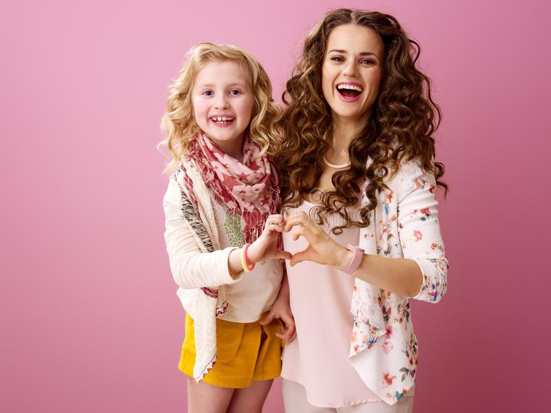 显示心形的手的微笑的时髦的母亲和女儿 免版税库存图片
