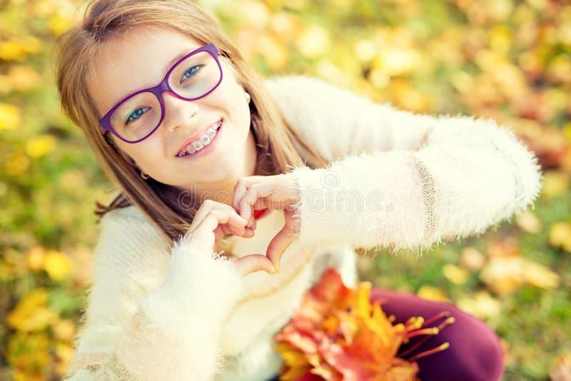 戴显示心脏用手的括号和眼镜的微笑的小女孩 Autum时间 免版税库存图片