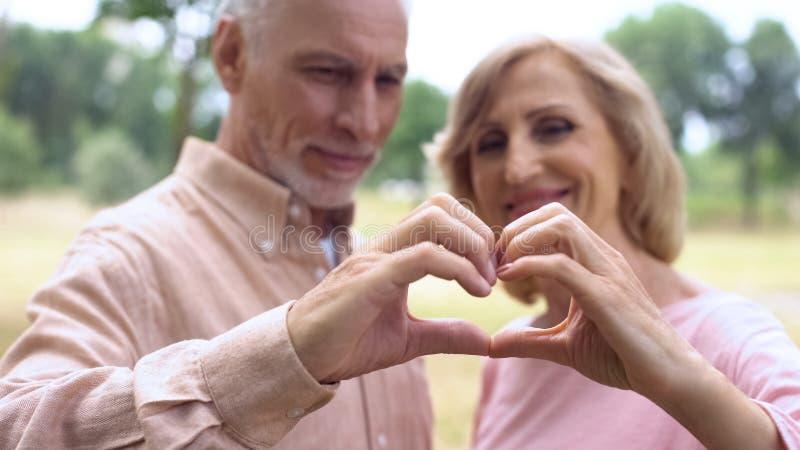 显示心脏的愉快的资深夫妇打手势,爱统一性,言情的知己 免版税库存图片