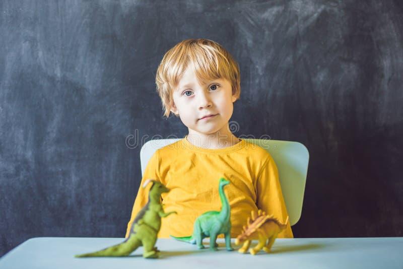 显示恐龙的男孩作为古生物学家 免版税库存图片
