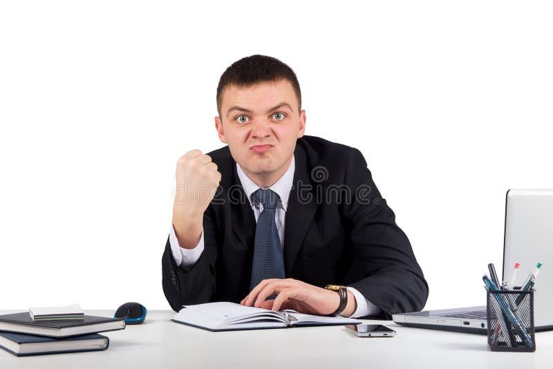 显示您他的拳头的一个年轻恼怒的商人的画象隔绝在白色背景 库存照片
